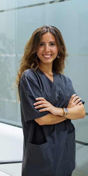 Beautiful confident woman doctor dentist wearing blue lab coat looking at camera